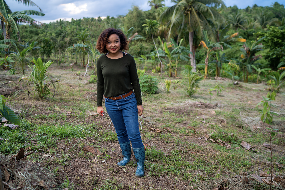 Louise Mabulo stands in front of trees and plants of the agricultural area of the Philippines where she works in sustainable agriculture in cacaor
