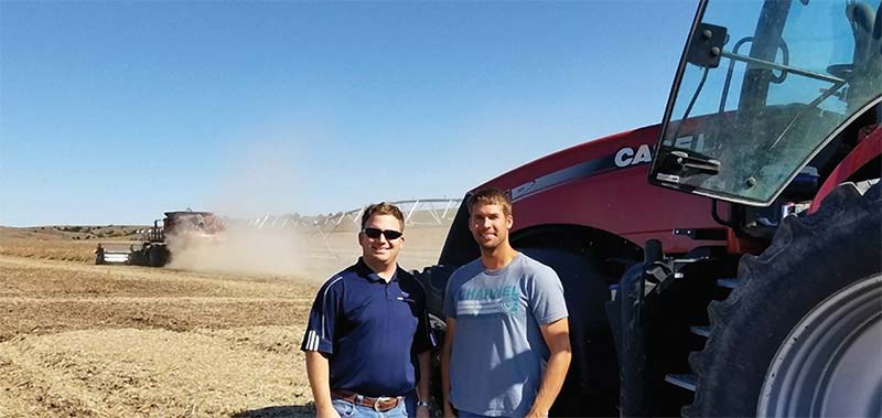 Ty Schurr and Dustin Olson in field during harvest