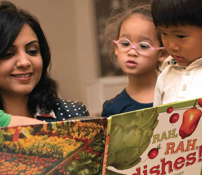 preschoolers reading book about vegetables with educator