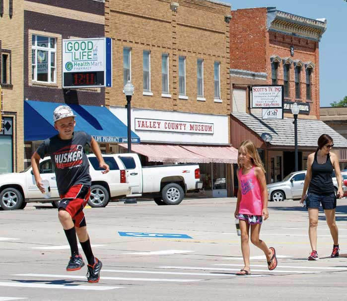 youth crossing rural street downtown