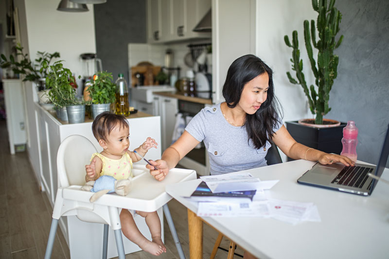 Woman working on laptop next to toddler in high chair.